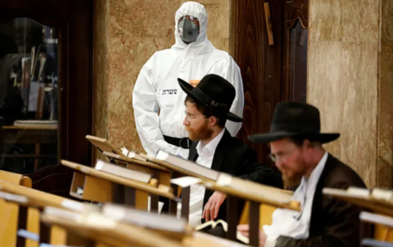 An Israeli police officer wearing protective gear waits to detain Ultra-Orthodox men as they pray in a synagogue, Bnei Brak, April 2, 2020.Credit: AP Photo/Ariel Schalit
